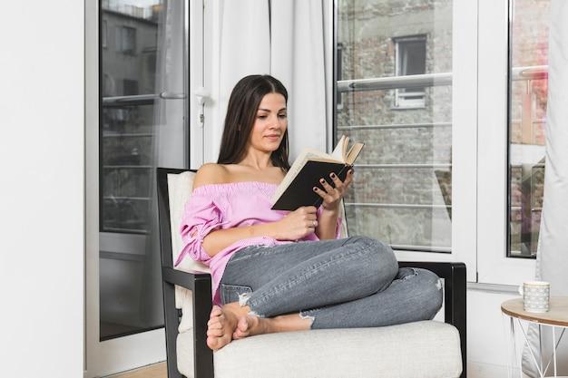 Mujer bastante joven que se sienta en la silla que lee el libro en casa