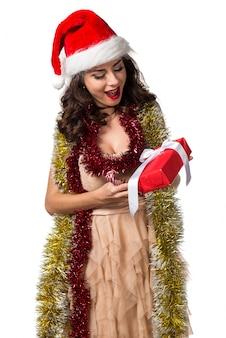 Mujer bastante joven que sostiene un regalo de la navidad. concepto de navidad