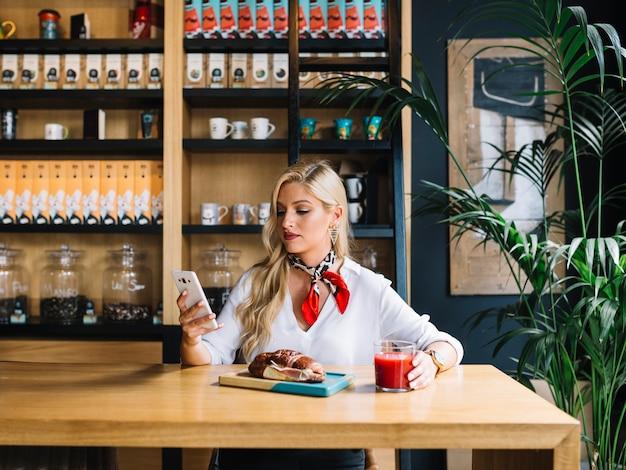 Mujer bastante joven que usa el teléfono móvil que sostiene el vidrio de jugo en caf�