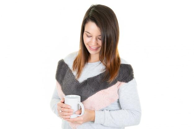 Mujer bastante joven relajante mirando hacia abajo sosteniendo una taza de café o una taza de té