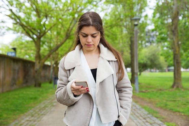 Mujer bastante joven seria que usa smartphone en parque