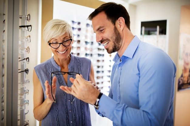 Mujer bastante madura está eligiendo gafas nuevas en la tienda de óptica