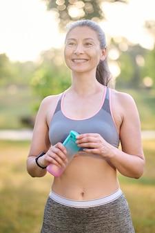 Una mujer bastante madura en ropa deportiva sonriendo muy bien