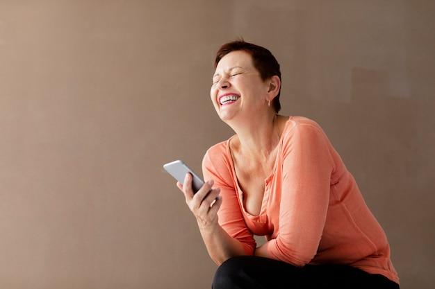 Mujer bastante madura con teléfono riendo