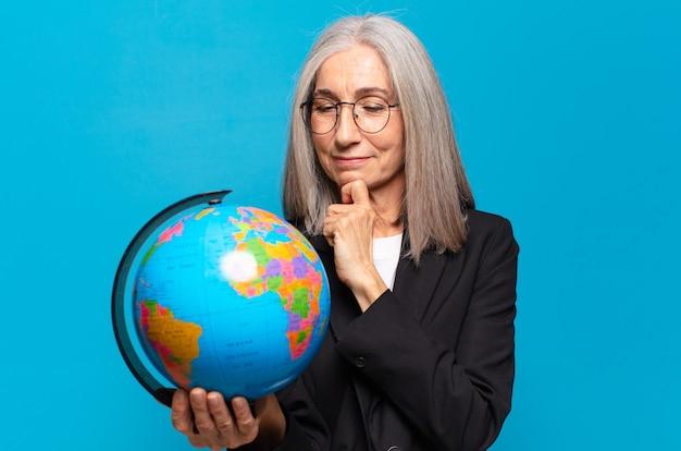 Mujer bastante mayor con un globo terráqueo. concepto de mundo