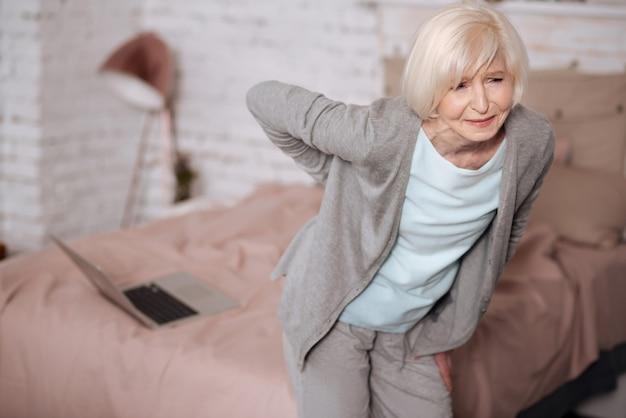 Mujer bastante mayor de pie y sintiendo malestar debido al dolor en la espalda.