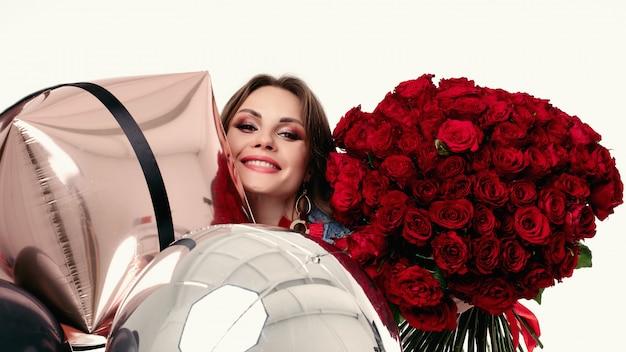 Mujer bastante positiva con maquillaje sosteniendo ramo de rosas rojas y globos de aire.