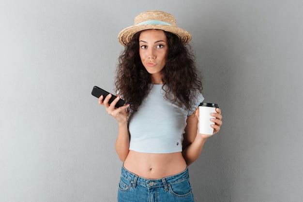 Mujer bastante rizada con sombrero con taza de café y teléfono inteligente mirando a la cámara sobre fondo gris