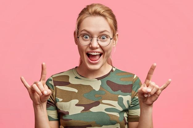 La mujer bastante sorprendida hace un signo genial, hace gestos con las manos y tiene una expresión feliz, vestida con una camiseta informal, aislada sobre rosa