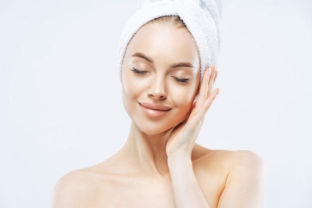 Mujer bastante tranquila con una toalla envolvente en la cabeza, cierra los ojos, disfruta de la suavidad de la piel, se somete a un tratamiento para el cuidado de la piel, se para los hombros descubiertos en el interior, relajada después del baño, aislada sobre fondo blanco