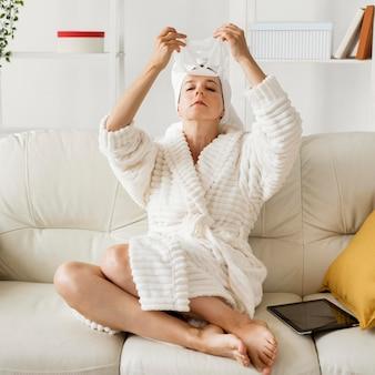 Mujer en bata de baño aplicando mascarilla facial en el sofá