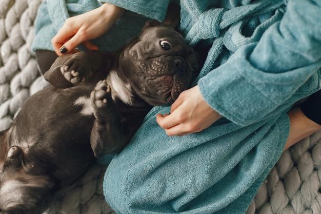 Mujer en una bata de baño azul con bulldog negro