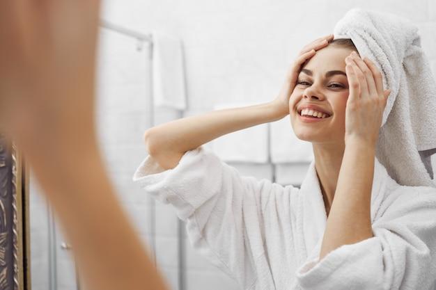 Una mujer en una bata de baño en una bata de baño delante de un espejo se mira a la cara