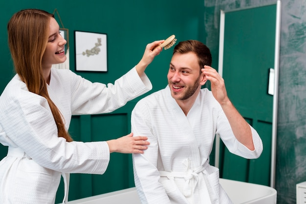 Mujer en bata de baño cepillando el cabello del hombre