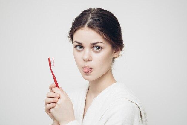 Mujer en bata de baño cepillarse los dientes
