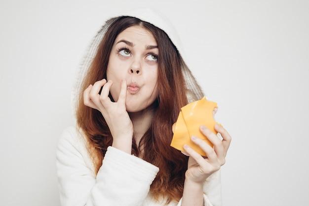Mujer en una bata de baño comiendo un sándwich en casa