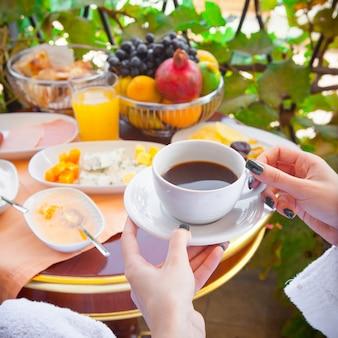 Mujer en una bata de baño desayunando con café afuera en la mañana