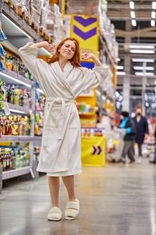Mujer en bata de baño estirando los brazos en el supermercado, ella es la primera compradora de la mañana, en el pasillo