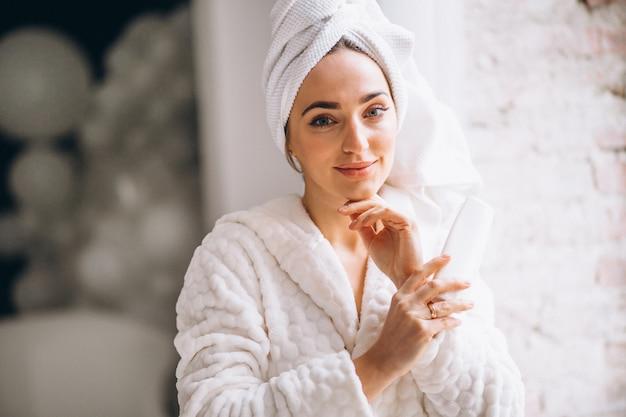 Mujer en bata de baño con loción corporal.