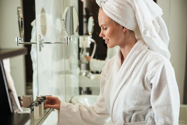 Mujer en bata de baño mirando cosméticos cerca de espejo