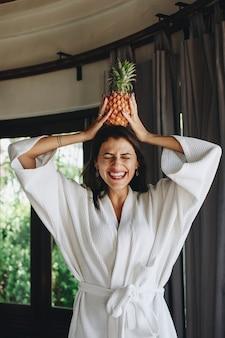 Mujer en una bata de baño sosteniendo una piña
