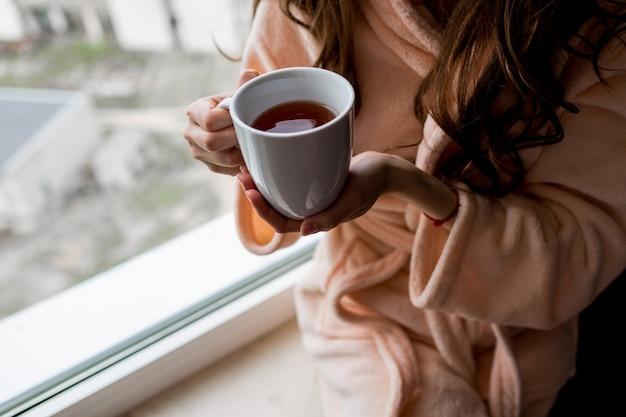 Mujer en bata de baño sosteniendo una taza de té caliente. estado de ánimo de otoño.
