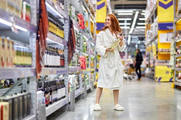Mujer en bata de baño vino a comprar alcohol en la tienda, ella está sonriendo de pie en el pasillo