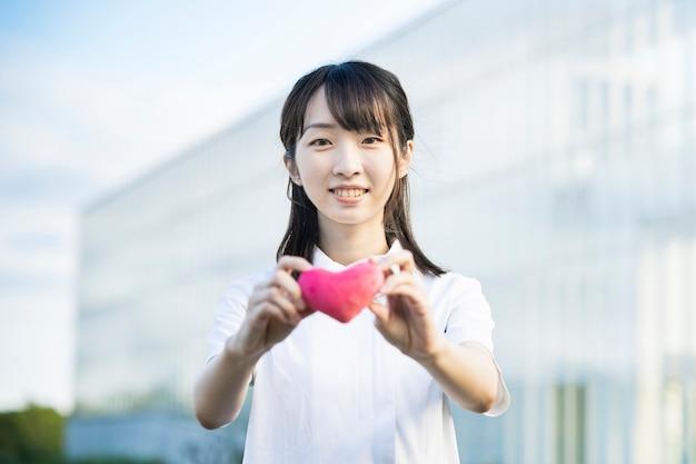 Una mujer con una bata blanca con un accesorio en forma de corazón.