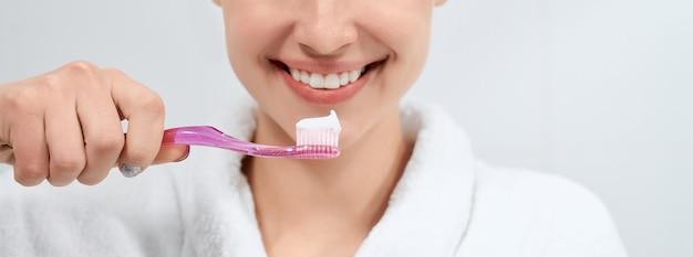 Mujer en bata blanca con cepillo de dientes con pasta