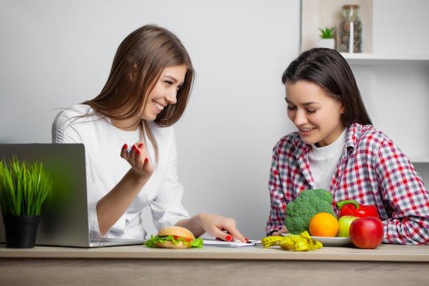 Mujer en la bata blanca nutricionista escribe un programa de dieta saludable para bajar de peso