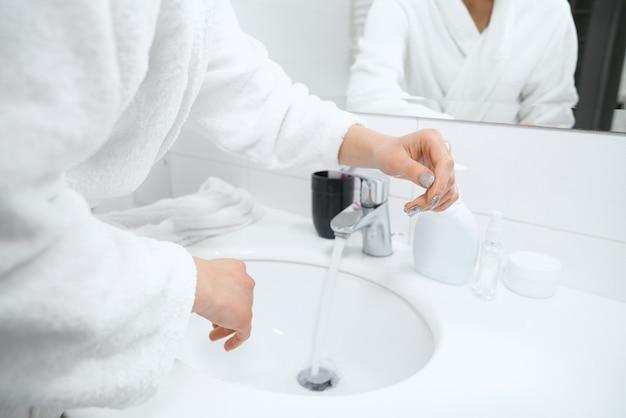 Mujer en bata blanca de pie cerca del fregadero y lavarse las manos