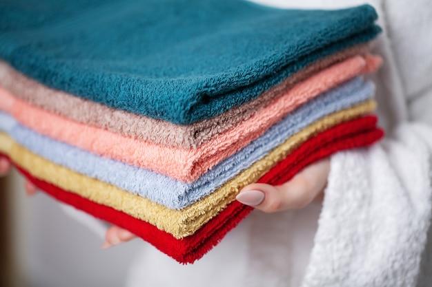 Mujer en una bata blanca con una pila de toallas de colores