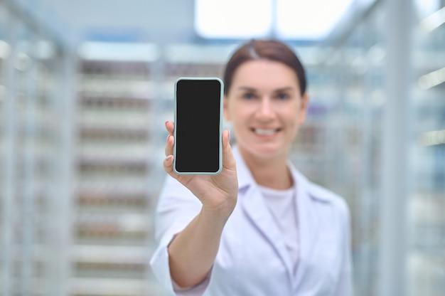 Mujer en bata médica que muestra la pantalla del teléfono inteligente