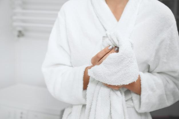 Mujer en bata de pie en el baño con toalla blanca