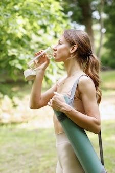 Mujer bebe agua de botella en el entrenamiento de verano en el parque