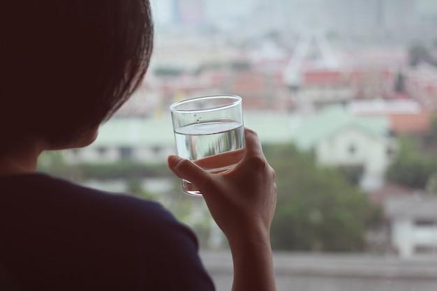 La mujer bebe agua para una buena salud