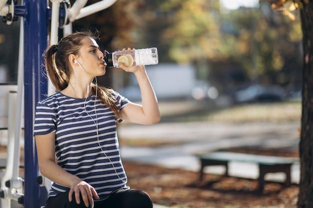 Mujer bebe agua de una coctelera después del entrenamiento.