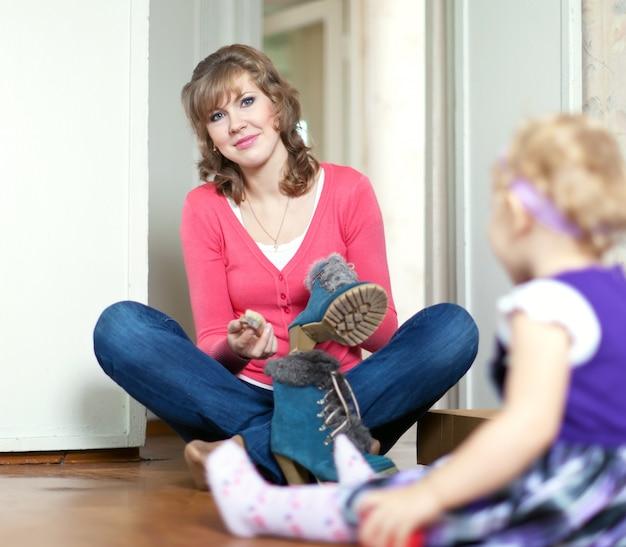 La mujer con el bebé limpia el calzado