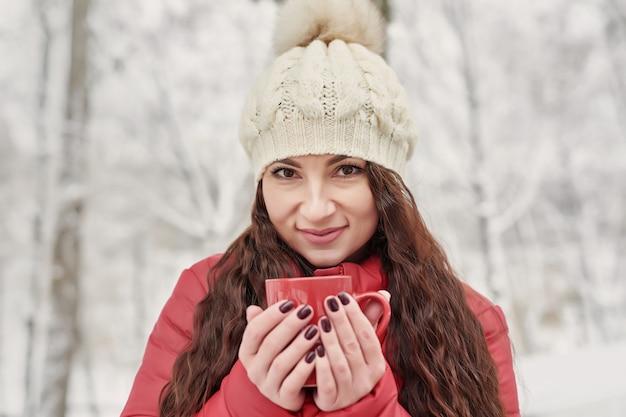 Mujer bebe té o café caliente de la taza en el acogedor jardín de la casa cubierto de nieve en la mañana de invierno. hermosa mujer disfrutando de invierno al aire libre con taza de bebida caliente. vacaciones navideñas. acogedor estilo de vida invernal.
