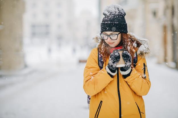 Mujer bebe té o café caliente de una taza acogedora en la nevada mañana de invierno al aire libre