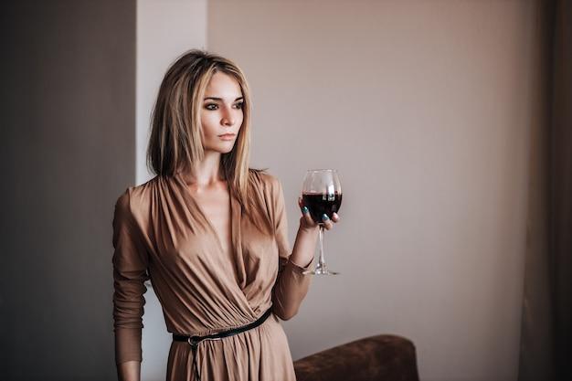 Una mujer bebe vino tinto en un restaurante