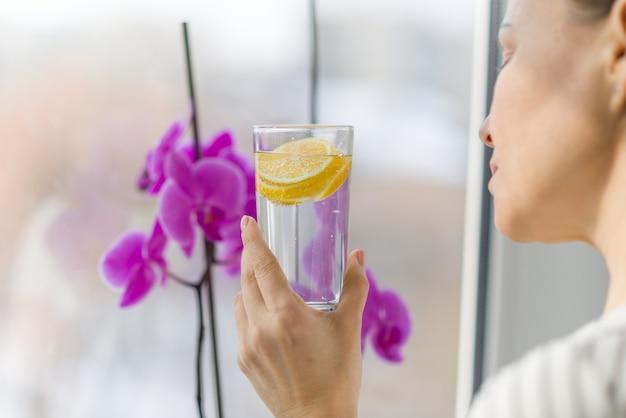 Mujer beber agua con limón orgánico fresco