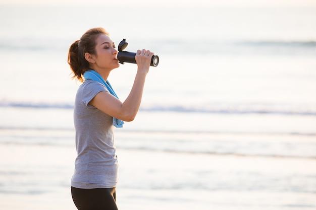 Mujer bebiendo agua después del ejercicio.