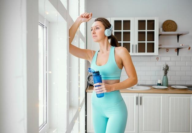 Mujer bebiendo agua después del entrenamiento