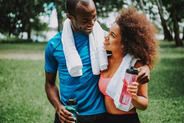 Mujer bebiendo agua después de hacer ejercicio pareja juntos en el parque