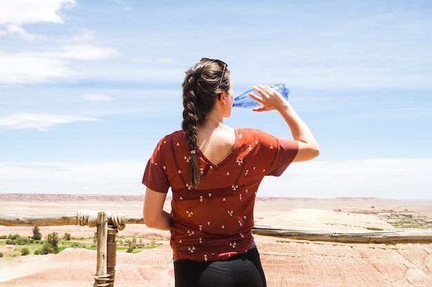 Mujer bebiendo agua en un paisaje desértico desde atrás