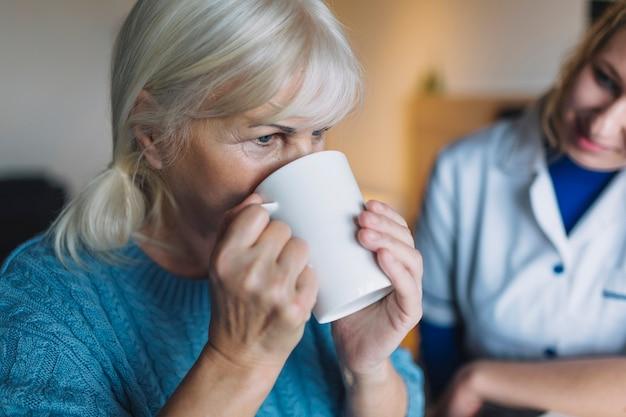Mujer bebiendo en asilo de ancianos