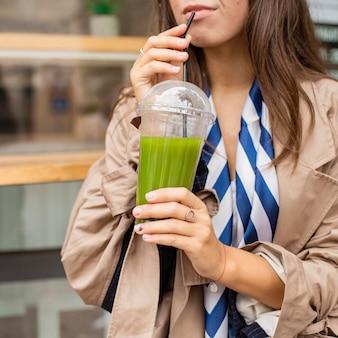 Mujer bebiendo batido verde