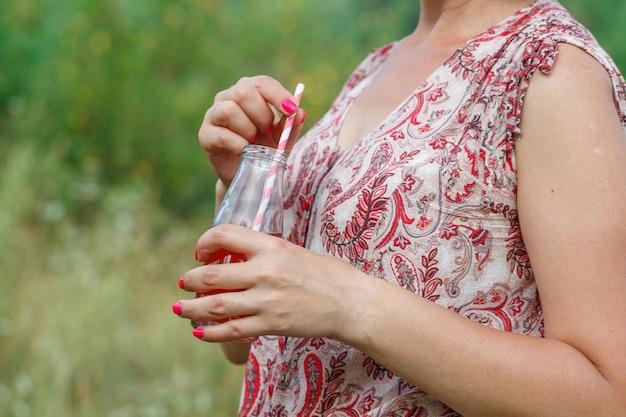 Mujer bebiendo bebida de desintoxicación al aire libre