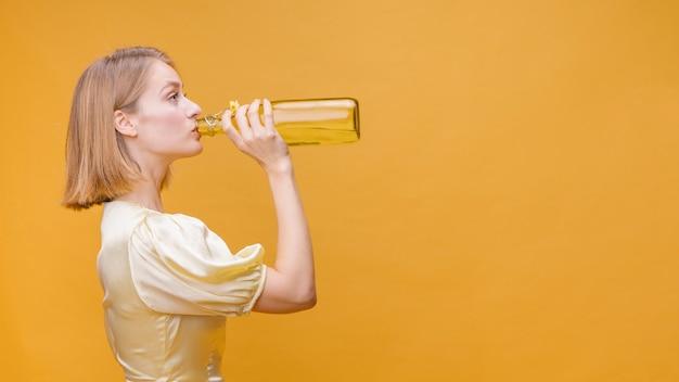 Mujer bebiendo de una botella en un escenario amarillo